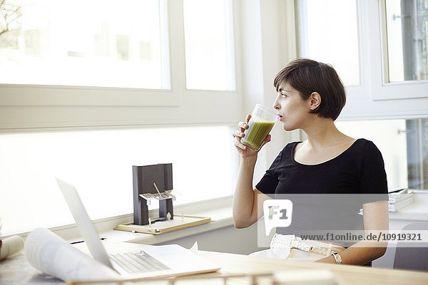 Porträt einer Frau  die im Büro grünen Smoothie trinkt
