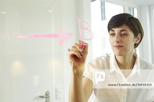 Porträt einer Frau,  die in einem Büro auf einer Glasscheibe schreibt