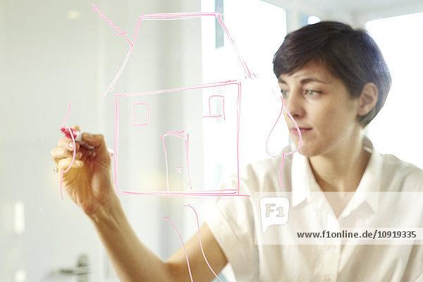 Frau beim Zeichnen eines Hauses auf Glasscheibe in einem Büro