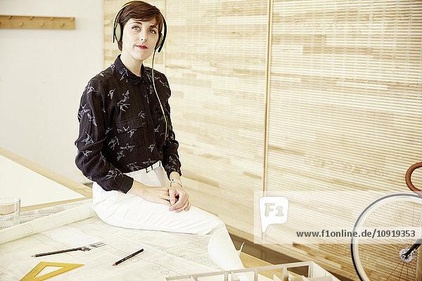 Frau beim Musikhören mit Kopfhörern im Büro