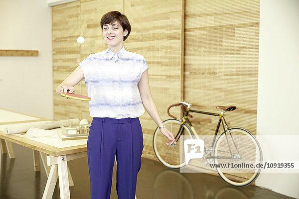 Porträt einer lächelnden Frau,  die mit Tischtennisschläger und Ball im Büro spielt.
