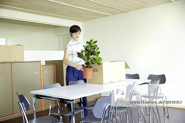 Frau mit Topfpflanze im neuen Büro