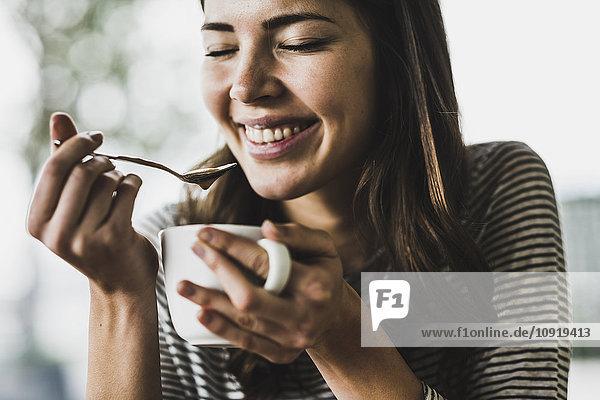 Junge Frau trinkt Cappuccino  Löffelchen Milchschaum