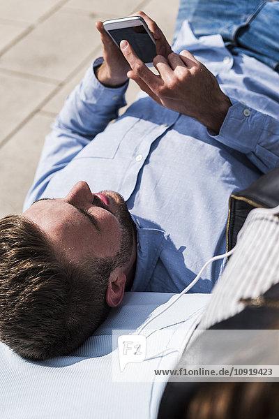 Junger Mann auf der Bank liegend mit Smartphone