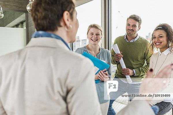 Drei glückliche Kollegen im Büro  die eine sprechende reife Frau anschauen.
