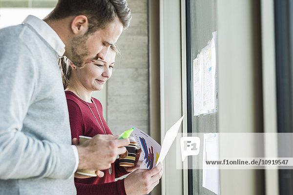 Zwei Kollegen am Bürofenster beim Blick auf Papier