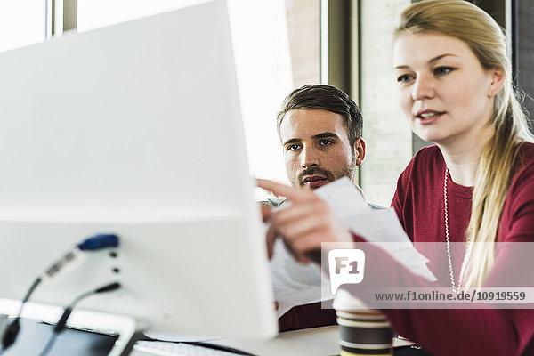 Zwei Kollegen am Schreibtisch mit Blick auf den Computerbildschirm