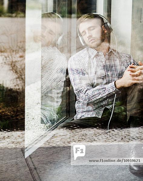 Junger Mann mit Kopfhörer am Fenster sitzend