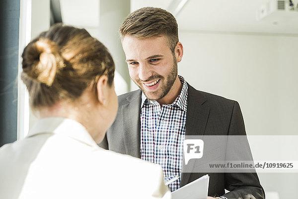 Lächelnder junger Mann mit Blick auf einen Kollegen im Büro