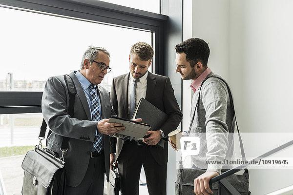 Drei Geschäftsleute mit digitalem Tablett sprechen im Treppenhaus