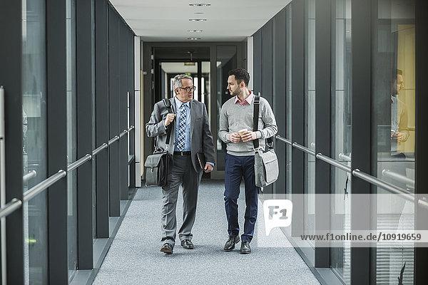 Zwei Geschäftsleute  die auf der Büroetage spazieren und reden.