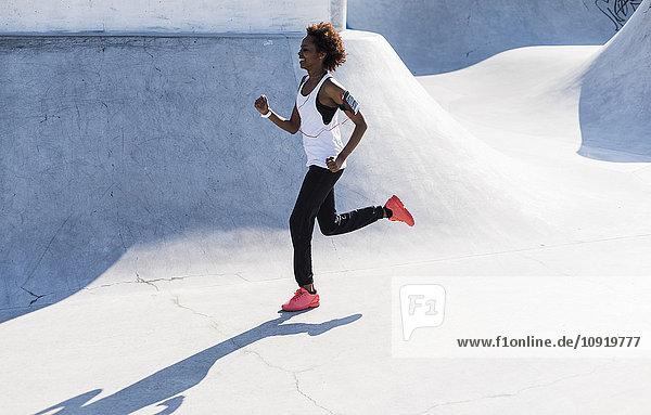 Junge Frau läuft im Skatepark