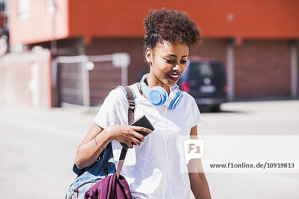 Lächelnde junge Frau mit Kopfhörer und Handy im Freien