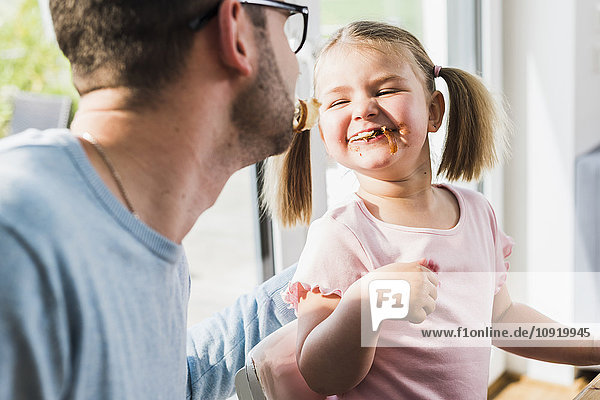 Playful father and daughter with food in mouth