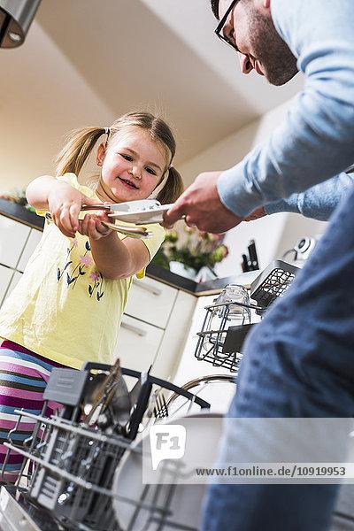 Tochter hilft Vater beim Geschirrspülen