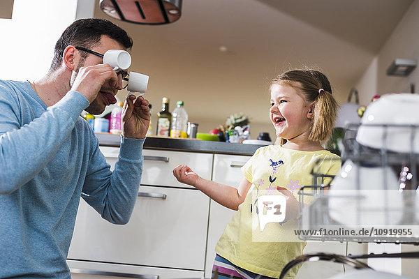Verspielte Tochter und Vater beim Geschirrspülen