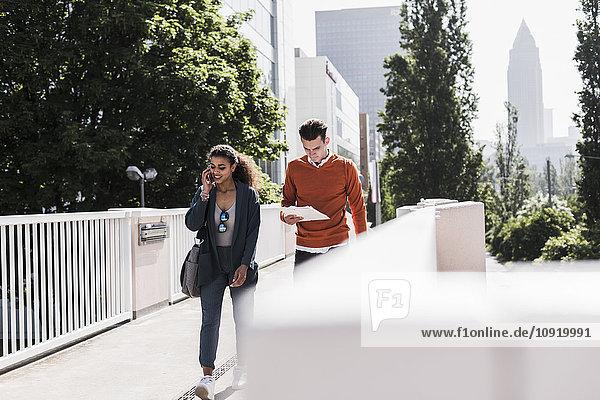 Junger Mann und Frau mit Handy und Dokument im Freien