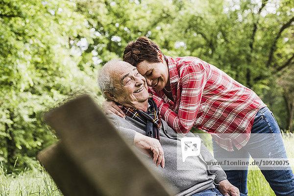 Glückliche Frau umarmt ihren alten Vater auf einer Bank in der Natur.