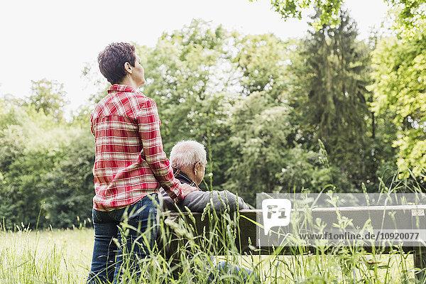 Frau und ihr alter Vater entspannen sich in der Natur