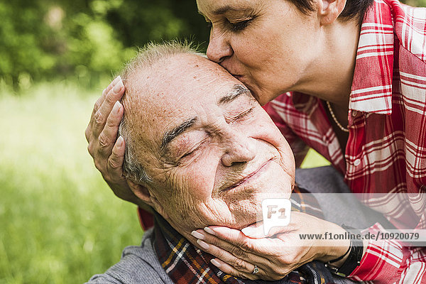 Porträt eines glücklichen älteren Mannes  der von seiner Tochter geküsst wurde.