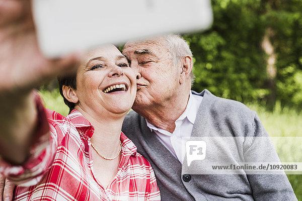 Frau nimmt Selfie mit ihrem alten Vater in der Natur