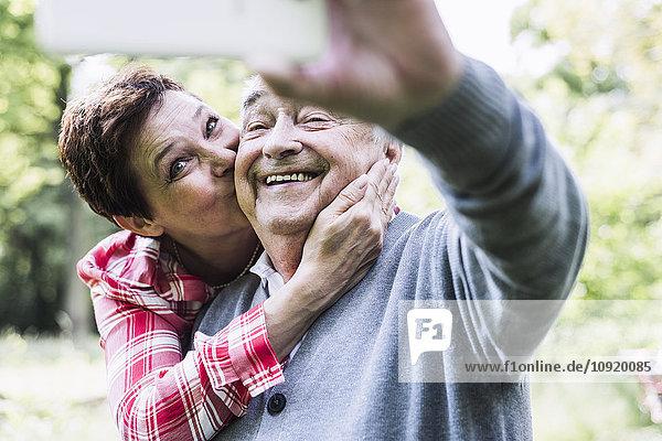 Glücklicher älterer Mann  der Selfie mit seiner Tochter nimmt.
