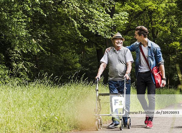 Glücklicher Großvater  der mit seinem Enkel in der Natur spazieren geht.