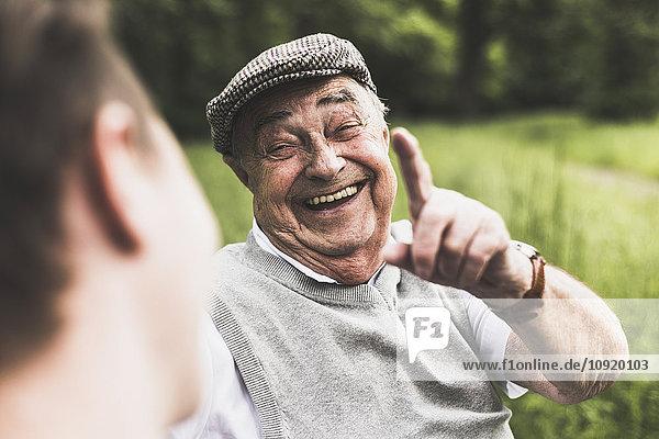 Porträt eines lachenden älteren Mannes im Gespräch mit seinem Enkel