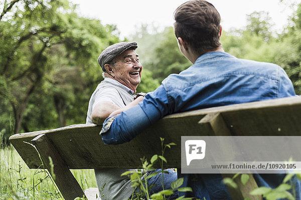 Lachender älterer Mann  der mit seinem Enkel auf einer Bank sitzt.
