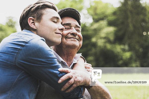 Glücklicher älterer Mann Kopf an Kopf mit seinem Enkel