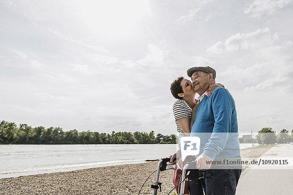 Älterer Mann und seine Tochter stehen am Flussufer.