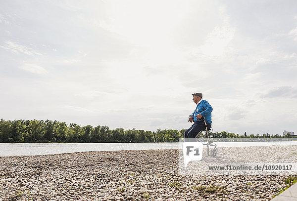Älterer Mann sitzt auf einem Rollator am Flussufer.