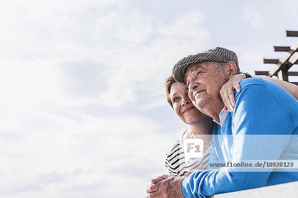 Älterer Mann und seine Tochter schauen gemeinsam in die Ferne.