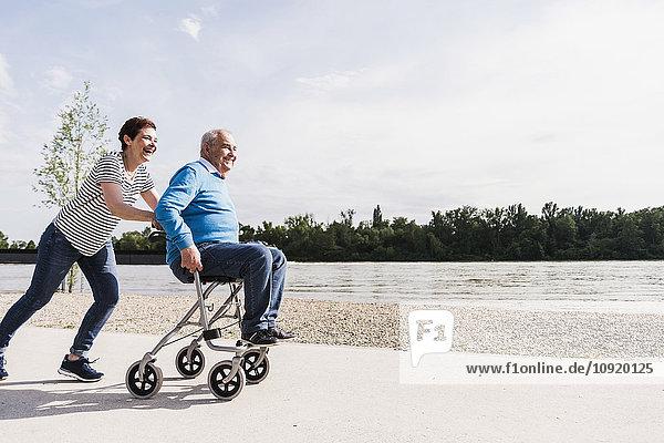 Frau schiebt ihren alten Vater  der auf einem Rollator sitzt.