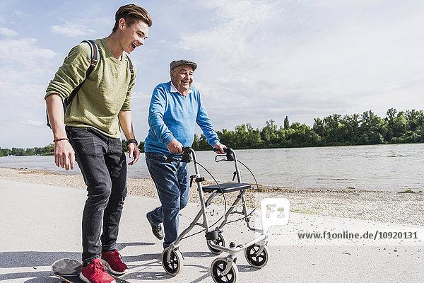 Großvater und Enkel beim gemeinsamen Spaziergang am Flussufer