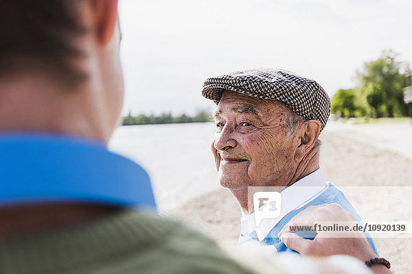 Porträt eines lächelnden älteren Mannes  der seinen Enkel ansieht.