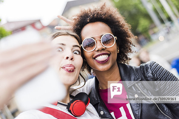 Two women sticking out tongues while taking selfie with smartphone