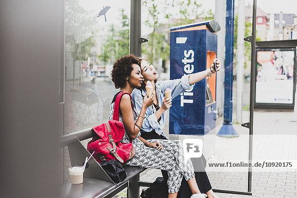 Zwei Frauen mit Eiszapfen sitzen an der Bushaltestelle und nehmen Selfie mit Smartphone.