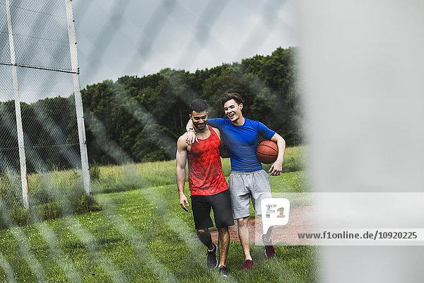 Zwei glückliche Männer mit Basketball beim Verlassen des Sportplatzes