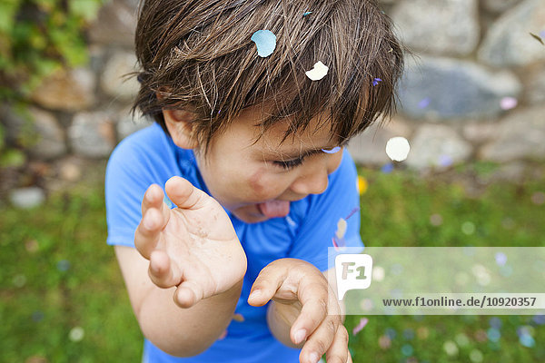 Lttle boy playing with confetti