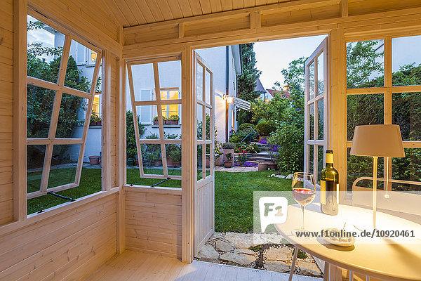 Rotweinglas und Flasche und Schale mit Oliven auf dem Tisch in einem Gartenhäuschen