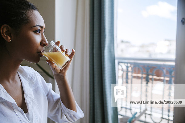 Young woman drinking glass of juice while looking through window