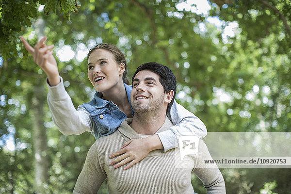 Junger Mann trägt seine Freundin huckepack in der Natur.
