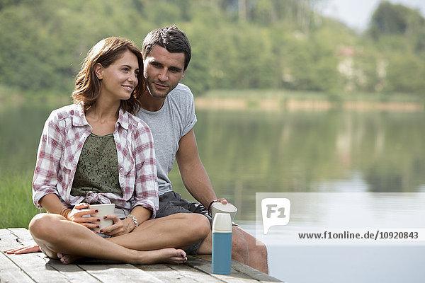 Porträt eines entspannten jungen Paares mit Kaffeetassen am Steg am See