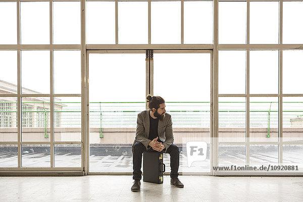 Hipster Geschäftsmann mit Aktentasche vor der Tür im Industriebau