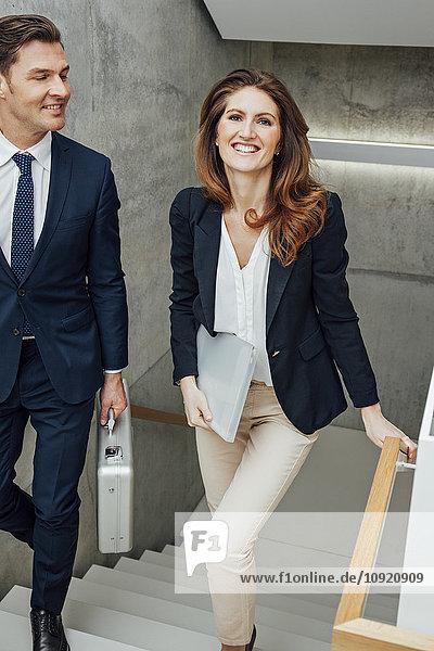 Zwei lächelnde Geschäftskollegen im Treppenhaus