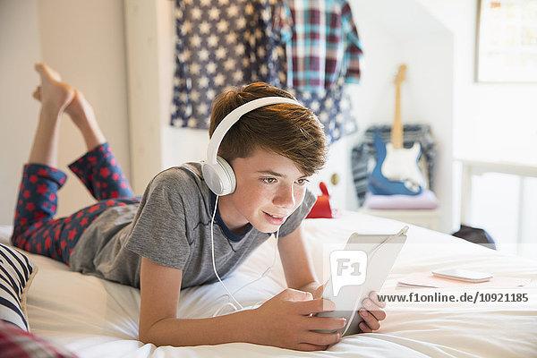 Junge mit Kopfhörer  der Musik auf einem digitalen Tablett hört.