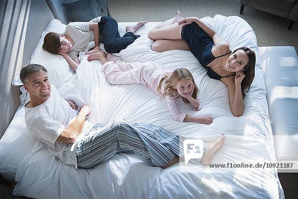Porträt einer lächelnden Familie im Pyjama  die sich im Bett entspannt.