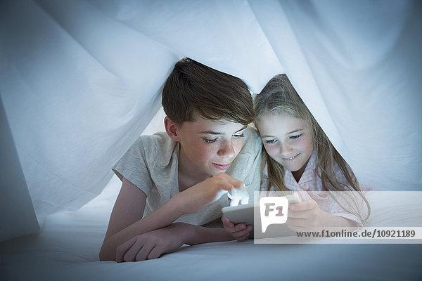 Bruder und Schwester teilen sich ein digitales Tablett unter dem Blatt