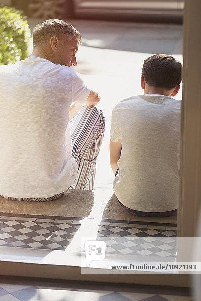 Vater und Sohn unterhalten sich auf der Vordertreppe